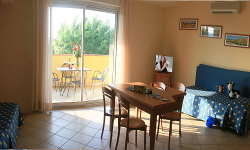 Family rooms in Manerba del Garda, for two adults and children.A bedroom for the couple, a room with beds for the children, a living area with a kitchenette on request. The room has a large bathroom with shower.A large covered balcony with table and chairs. Family vacation for 5 guests